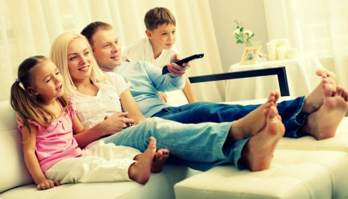 Portrait of happy family with two children sitting on sofa and watching TV
