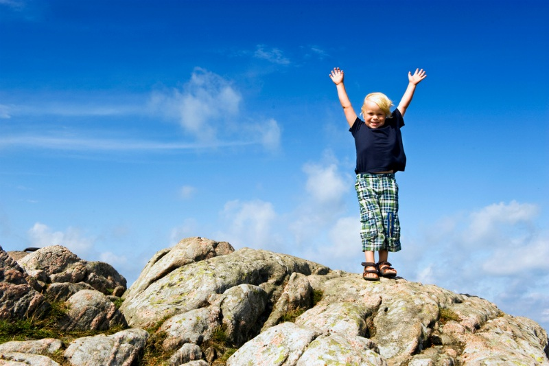 Young boy with his arms raised in victory on top of a rock, conceptual image for conquering challenges, pushing the boundaries, and continuous improvement