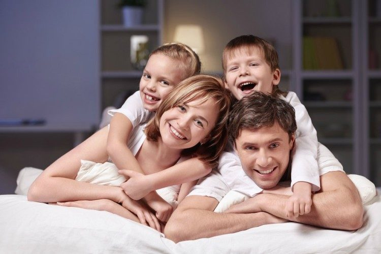 Families with children in bed at night at home