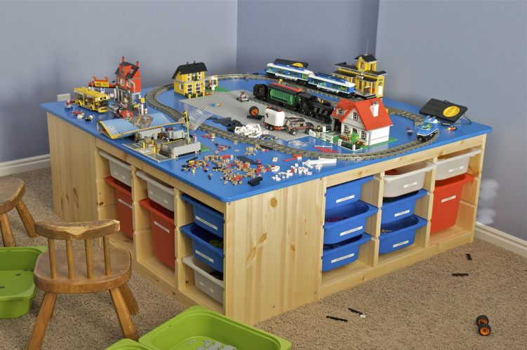 "This is the table I built for my kids' LEGO collection for Christmas 2009.  The base is made from four slotted organizers from IKEA. The bins (also from IKEA) are made to slide into all the nice slots.  The table top is made from a 5' x 5' piece of baltic birch plywood cut to 4' 8"". I rounded the corners of the top, routed 1/8"" edge, and sanded it using an orbital sander. I then used spray paint (first coat is white primer, then royal blue -- which matched the blue LEGO color exactly, and then a clear coat) bought from Home Depot.  The kids love it and so do I since their LEGO stuff is now much more organized and stays in one area of the house (though it looks kinda messy in this pictures because of being in the middle of a few new projects)."